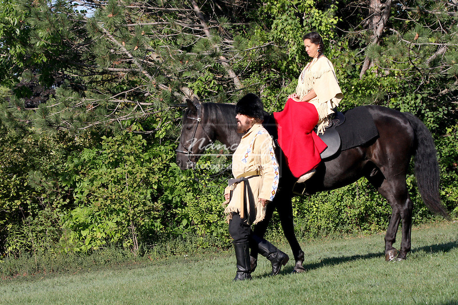 A Native American Indian woman riding a black horse with a pioneer