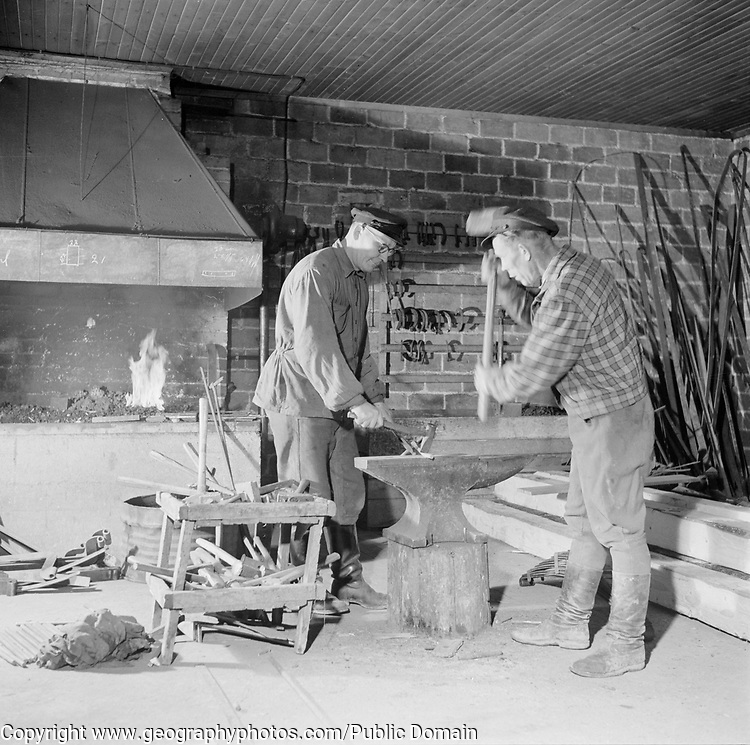 Two men working with metal blacksmith forge, Finland, 1950s