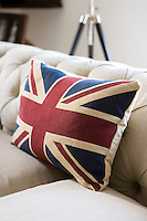 A large scatter cushion with a Union Jack motif creates a colourful accent against the natural linen upholstery of a contemporary chesterfield sofa