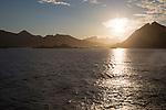 Midnight sun low in sky over mountains near Stamsund, Lofoten Islands, Nordland, Norway
