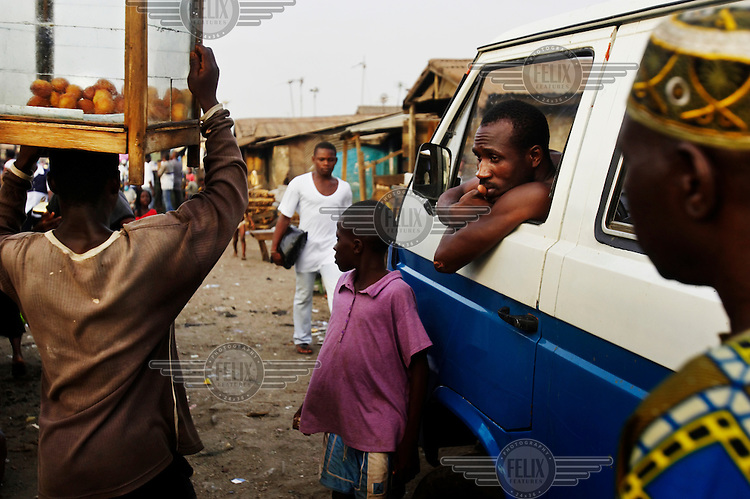 A mini bus driver watches pedestrians at a market in Lagos.