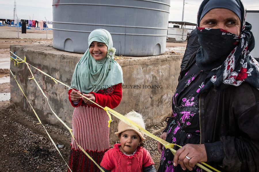 IRAK, Khazer: A young displaced girl is watching people lining up for food in front of her in the IDP's camp of Khazer, the 5th december 2016.<br /> <br /> IRAK, Khazer: Une jeune fille d&eacute;plac&eacute;e dans le camp de Khazer regarde les gens faire la file pour de la nourriture dans le camp de Khazer, le 5 d&eacute;cembre 2016.