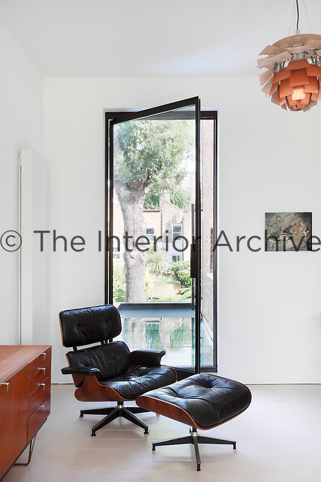 A classic black leather and wood armchair and ottoman by Charles Eames is placed in front of a full height glazed pivot door and glass which gives views to the garden from the lounge.
