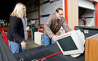 NWA Media/DAVID GOTTSCHALK - 12/31/14 - Amber Sharp,  left, household hazardous waste operator, assists Craig Edmonston (cq), right,  with a computer, cords and a television Wednesday December 31, 2014 at the Washington County Environmental Affairs and Recycling Household Hazordous Waste Drop-Off in Fayetteville. The facility along with Boston Mountain Solid Waste in Prairie Grove,  has eliminated fees for up to 10 items through January 16, 2015.