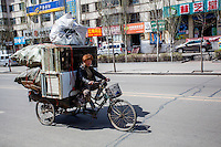 Woman hauling a large load on a carted bicycle in Datong, China