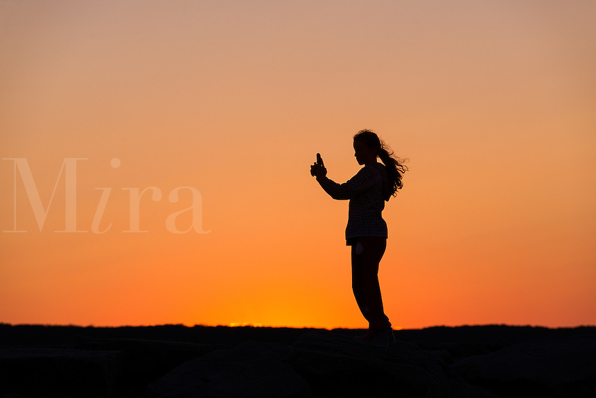 Girl with mobile phone enjoys the sunset from a jetty.