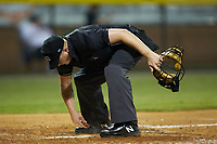Home plate umpire West Hyer cleans home plate during the Appalachian League game between the Danville Braves and the Burlington Royals at Burlington Athletic Stadium on August 9, 2019 in Burlington, North Carolina. The Royals defeated the Braves 6-0. (Brian Westerholt/Four Seam Images)
