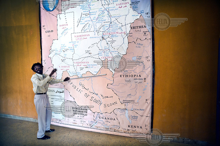 A Sudanese man standing in front of a map of part of N E Africa, displayed in the lobby of the National Museum discuss the new shape of their country following the independence of South Sudan.