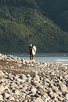 Single surfer in wetsuit on rocky beach with native bush in background. Mangaumanu, Kaikoura Coast.