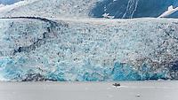 Small boat approaching the vast Harriman Glacier in Alaska, USA
