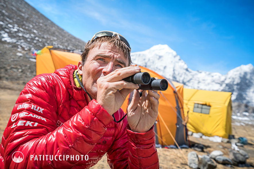 Ueli Steck using binoculars to look at Shishapangma's south face during the climbing expedition to the 8000 meter peak Shishapangma, Tibet
