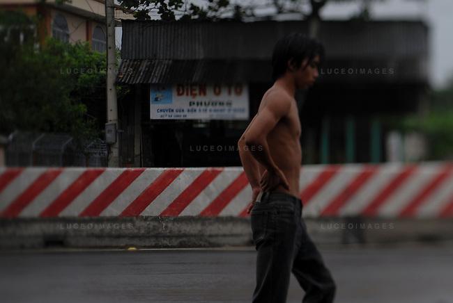 A Vietnamese boy walks in the rain outside of Ho Chi Minh City, Vietnam.
