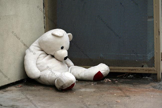 Stock Photo of a Teddy Bear Stuffed Animal Sitting with Head Down Near Alley Dumpster