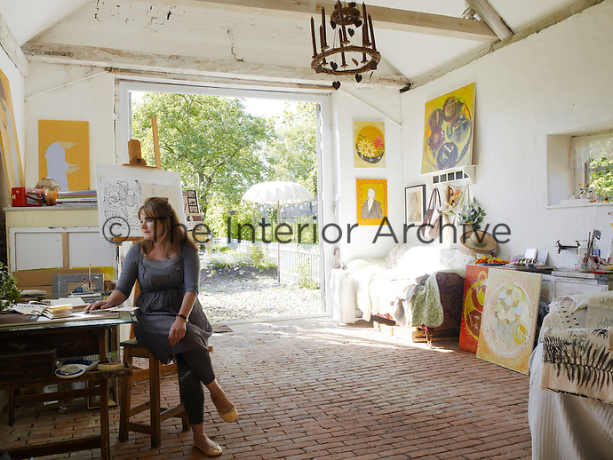 Sheila Scholes sitting at the work table in the studio of her house in Norfolk