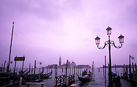 Beautiful graphic line up of group of gondolas ready for tourists in romantic Venice Ital