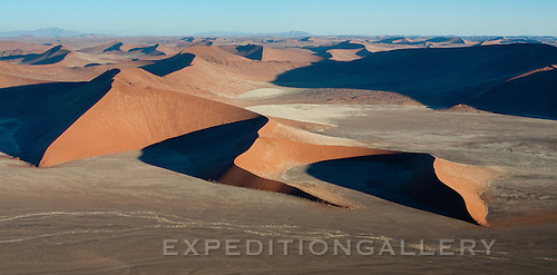 Aerial view of the enormous star-shaped sand dunes of the Sossusvlei region of Namib-Naukluft National Park, Namibia. These dunes are among the tallest in the world.