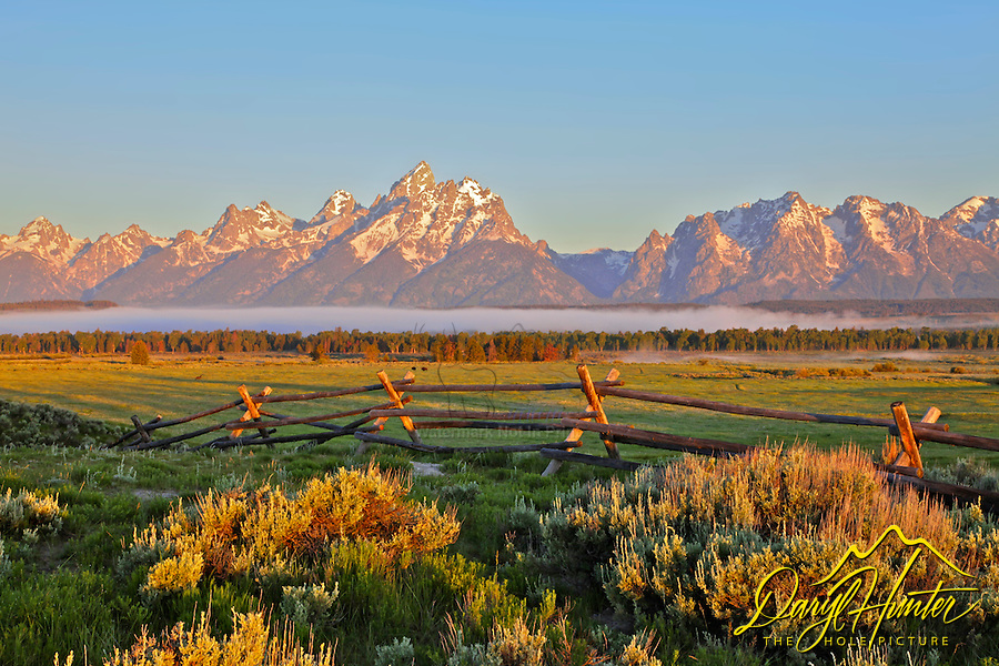 Grand Tetons at daybreak, a buckrail fence is a reminder of Grand Teton National Park's ranching legacy.