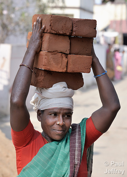 A woman carries bricks on her head at a construction site in Natham, a small town in the southern India state of Tamil Nadu.
