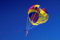 Girl in multicolored parasail against blue sky. Islamorada, Florida.