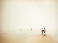 A couple strolls on the beach of North Carolina.