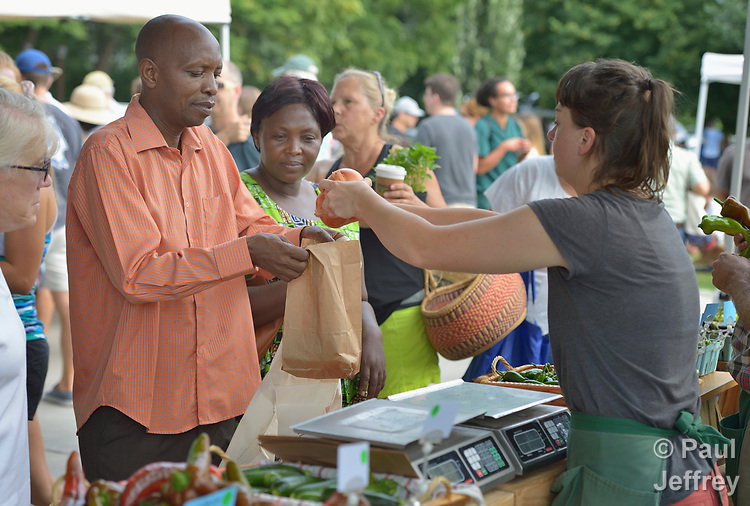 Casmil Ngundakumana, a refugee from Rwanda, buys produce in the Durham Farmers' Market in Durham, North Carolina. Ngundakumana was assisted on his arrival in Durham by Church World Service, which resettles refugees in North Carolina and throughout the United States.<br /> <br /> Photo by Paul Jeffrey for Church World Service.