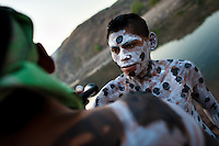 "A Cora Indian boy, with body and face painted all over, paints his mate before the religious ritual ceremony of Semana Santa (Holy Week) in Jesús María, Nayarit, Mexico, 21 April 2011. The annual week-long Easter festivity (called ""La Judea""), performed in the rugged mountain country of Sierra del Nayar, merges indigenous tradition (agricultural cycle and the regeneration of life worshipping) and animistic beliefs with the Christian dogma. Each year in the spring, the Cora villages are taken over by hundreds of wildly running men. Painted all over their semi-naked bodies, fighting ritual battles with wooden swords and dancing crazily, they perform demons (the evil) that metaphorically chase Jesus Christ, kill him, but finally fail due to his resurrection. La Judea, the Holy Week sacred spectacle, represents the most truthful expression of the Coras' culture, religiosity and identity."