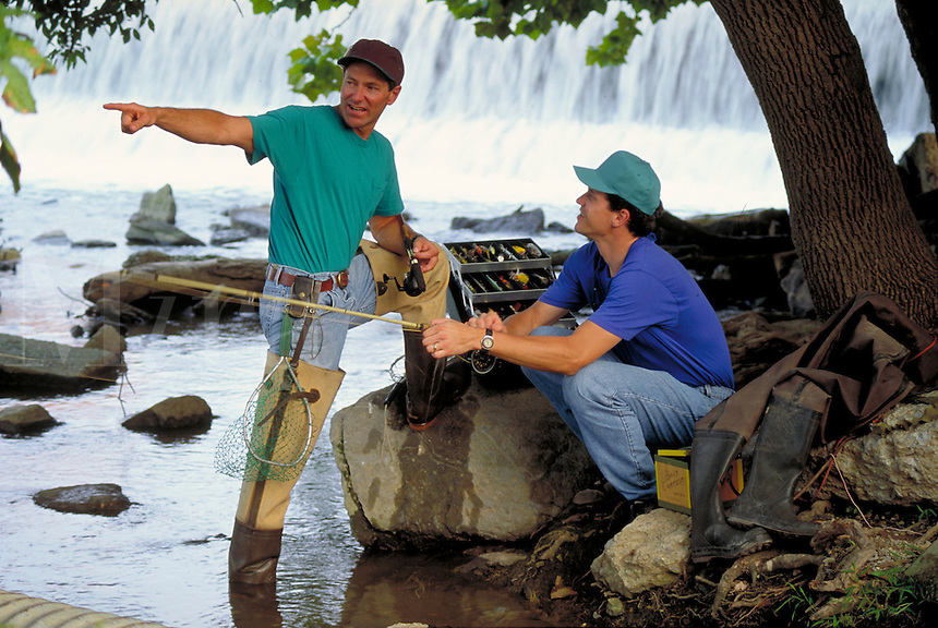 two young adult caucasian men with flyfishing gear discuss best fishing spot. flyfishermen. New Cumberland Pennsylvania United States Yellow Breeches Creek.