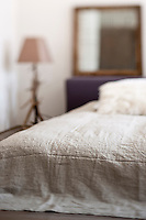 A low level bed is covered in a natural linen bedspread