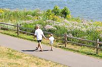 Dad and son walking along Lake Phalen Park shoreline path. St Paul Minnesota USA
