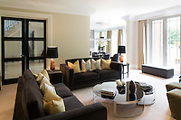 The spacious, semi-open plan sitting room is decorated in tones of grey and gold. Two sofas provide plenty of comfortable seating and the steel coffee table adds a contemporary note to the otherwise traditionally styled room.