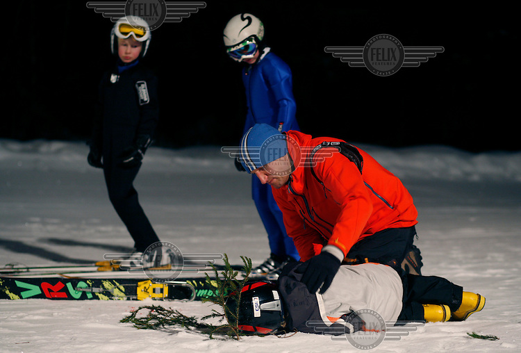 Lars Young Vik is comforted by his dad after taking a tumble in Schroderbakken ski jump.   Fabian Andersen and William Kalfoss looks on.