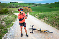 After crashing on her gravel bike, on the Italian Strade Bianche, a woman cyclist stands looking at her wounds.