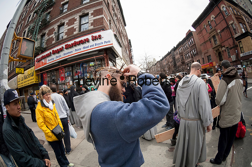 A member of the Franciscan Friars of the Renewal prepares his crown of thorns in Harlem in New York prior to the annual Way of the Cross Witness Walk on Good Friday, April 18, 2014. The procession starts at St. Joseph's Friary in Harlem and ends several hours later at the St. Crispin Friary in the Bronx where a Good Friday service takes place. Several hundred parishioners as well as clergy participated in the event, part of Holy Week,  which commemorates the crucifixion of Jesus Christ. (© Richard B. Levine)