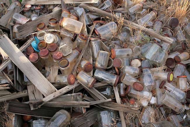 Old pile of rusty screw-top food jars in a dump