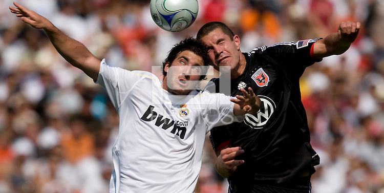 Real Madrid forward (20) Gonzalo Higuain goes up for a header with DC United defender (16) Greg Janicki during their friendly at FedEx Field in Landover, Maryland.  Real Madrid defeated DC United, 3-0.
