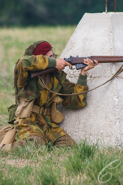 """Reenactors showcase World War II tanks, half-tracks and support vehicles during the Museum of the America G.I.'s annual Open House on March 29, 2008 in College Station, Texas. A reenactor portraying a British paratrooper takes cover behind a """"dragon's tooth"""" anti-tank fixture."""