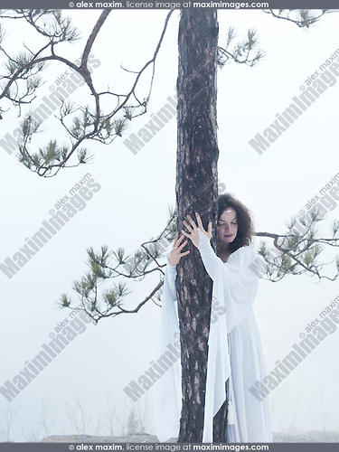 Young woman in white dress hugging a pine tree. Reconnecting with the nature.