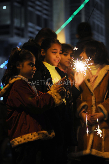 IRAQ, SULAIMANIYAH:  GIrls play with a sparkler on Salim Street in Sulaimaniyah...Revelers brought in the new year all across Kurdistan with shows of fireworks and enormous street parties...Photo by Kamaran Najm/Metrography