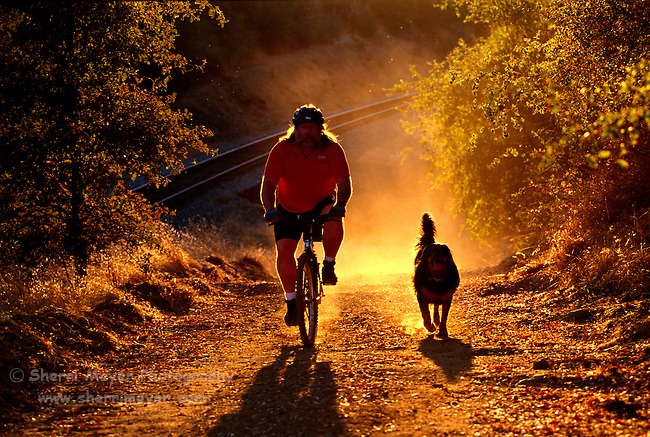 Man mountain biking with his dog