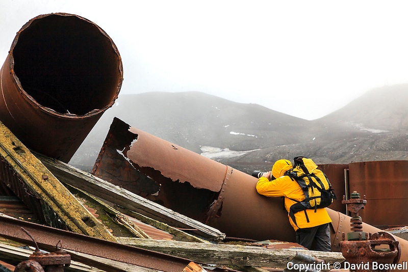 A photographer using a rusted pipe to steady his shot at Whalers Bay, an abandoned Norwegian whaling base on Deception Island in the South Shetland Islands, near the Antarctic Peninsula.