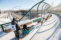 Robert Redington runs over the Tudor Road bridge during the Ceremonial Start of the 2017 Iditarod in Anchorage on Saturday March 4, 2017 <br /> <br /> Photo by Jeff Schultz/SchultzPhoto.com  (C) 2017  ALL RIGHTS RESVERVED
