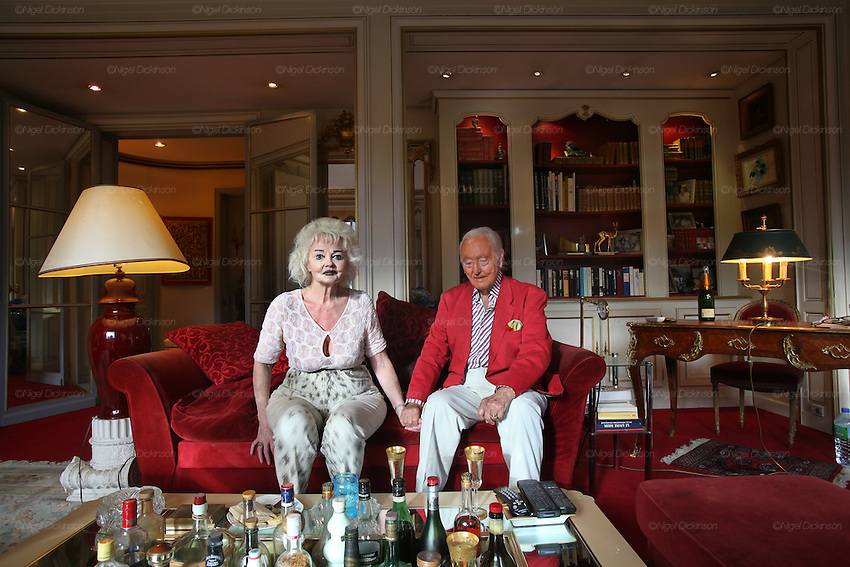 Wolf C Hartwig aged 91, producer of epic films and soft-porn features, with his fourth wife, and actress, Veronique Vendell in their apartment on Avenue de Foch, Paris. Wolf Hartwig was awarded a Bambi Award from German Cinema for his film 'The Iron Cross' which was directed by Sam Peckinpah starring James Coburn with Veronique Vendell. A producer working in exploitation genres, soft porn, sex, lurid, violent and sensational features. Other films he produced include 'Horrors from Spider Island'. 'Lady Hamilton' and 'Virgin of the Seven Seas'.//Wolf Hartwig and his wife Veronique Vendell sitting on sofa, Bambi award on bookshelf with other mementos