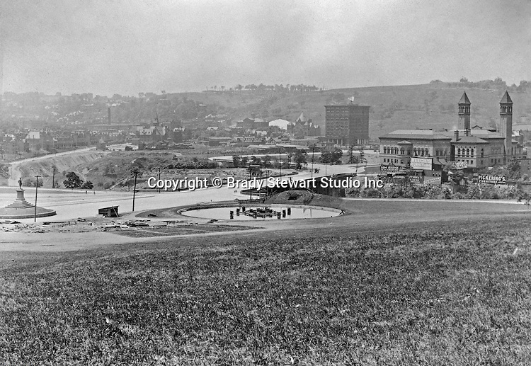 Oakland Section of Pittsburgh:  View of Schenley Park, Schenley Bridge and the Carnegie Institute from Flagstaff Hill - 1907.  Image includes the statue of Edward Manning Bigelow, Director of Public Works, and the Electric Fountain, bottom of Flagstaff Hill.  The Carnegie Institute (Library) is located to the right across the St Pierre Ravine.  The image includes the Schenley Bridge which was built in 1897 by architect Henry Rust.  Company signs near the Institue include: Keech's Furniture, Hershey's Cocoa, Tom Keene Cigars, Pickerings Furniture, Cubanola sheet music and Red Raven Splits.