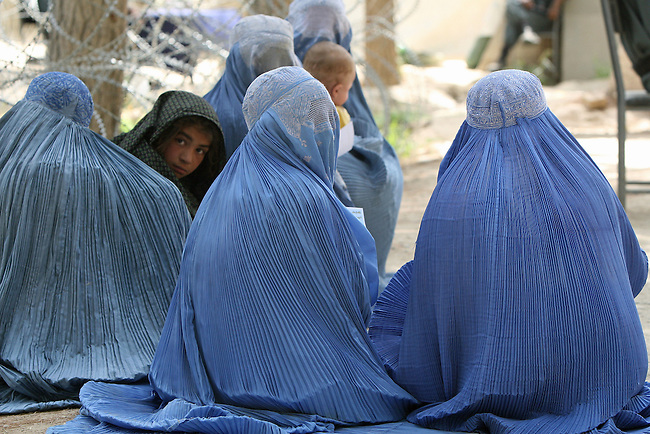 A girl peers out from a group of women clothed in burqas as they wait outside the district center of Shar-e-Safa in Zabul province, Afghanistan. U.S. troops provided medical care, and Afghan police distributed winter clothes, food staples and other relief items to about 200 people before they ran out of supplies.  Aug. 25, 2008. DREW BROWN/STARS AND STRIPES