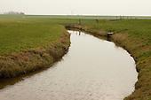 Buitendijks kweldergebied van waterschap Blija Buitendijks.<br /> Waterschap Blija Buitendijks is het kleinste waterschap van Nederland. Het waterschap beheert 100 hectare weiland, gelegen bij het dorp Blija in het noorden van Friesland, tussen de Waddenzeedijk en zomerdijk. Direct achter de 2,25 m +NAP hoge zomerdijk bevindt zich het uitgestrekte kweldergebied van de Waddenzee. Bij hoogwater (vloed) stroomt het buiten de zomerdijk gelegen kwelder regelmatig onder water. Bij extreem hoog water, bijvoorbeeld bij springtij en noordwesterstorm komt het zeewater vanuit de Waddenzee ook over de zomerdijk. De door het waterschap beheerde polder komt dan geheel onder water te staan, soms zelfs tot halverwege de Waddenzeedijk. Bij afgaand tij (eb) stroomt het zeewater via de klepstuwen in de zomerdijk terug naar de Waddenzee. De afgebeelde watergang (afwateringssloot) bevindt zich langs de zomerdijk met daarin de betonnen duiker met klepstuw. Op de achtergrond is de Waddenzeedijk (op Deltahoogte) te zien.