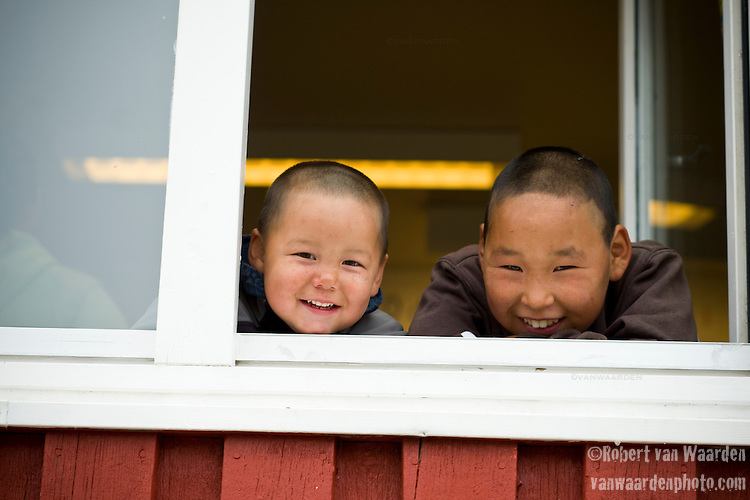 Two young boys stare out the school window in Tasiussaq, Greenland.