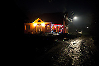 ROMANIA / Maramures / Valeni / 30 December / A brand new brightly colored villa sits decorated for Christmas on a muddy side path in the village of Valeni. Both children from the family had spent the last four years working in Ireland and sent back thousands of euros to their mother who was living in and old traditional wooden peasant home. In a matter of a few months a modern european style home has replaced the folk architecture. The look of Maramures villages is changing almost overnight.  © Davin Ellicson / Anzenberger