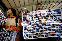Chinese university students sell auto pictures during the 2006 International Automotive Exhibition in Beijing, China..25 Nov 2006