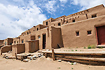 Traditional New Mexico adobe architecture against blue sky at Taos Pueblo in Taos, New Mexico.