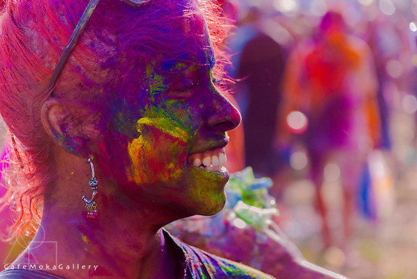 """Covered in """"Abir"""" this young lady is all smiles as she enjoys the frolic that is the Indian spring festival of Holi."""